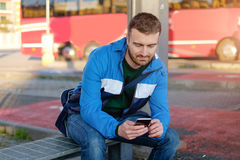 Man waiting at the bus station and looking at his smart-phone Stock Photography