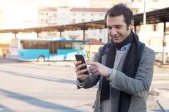 Man waiting at the bus station and looking at his smart-phone Royalty Free Stock Photo