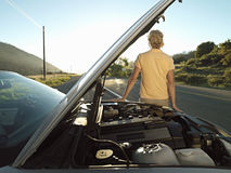 Man waiting beside car with open bonnet at roadside, experiencing problems with engine Stock Photos