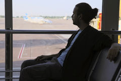 Man waiting flight in airport. Young man waiting his flight in airport lounge Stock Photo