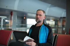 Man waiting flight at the airport. Thoughtful bearded man, traveler reading a book, waiting for the flight at the airport. Portrait of a bearded man on a blurred Royalty Free Stock Photo