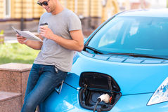 Man waiting for his car being charged Royalty Free Stock Images