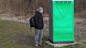 Man waiting near green portable toilet in the park. In spring day stock footage