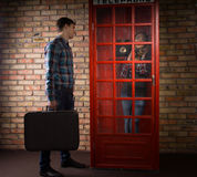Man waiting outside a phone booth for his wife Stock Photos