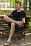 Man waiting. Sitting on a park bench Stock Photo