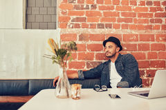 Man waiting for someone at cafe. Portrait of young man wearing hat sitting alone at a cafe with laptop on table. Man waiting for someone at coffee shop royalty free stock photos