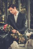 Man waiting someone in restaurant. Handsome man with bunch of red roses waiting his lady in restaurant Royalty Free Stock Images