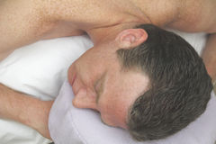 Man waiting to be massaged, face side, arms up. A man laying with his face to the side on a headrest, arms up on a massage table, waiting to be massaged Stock Images