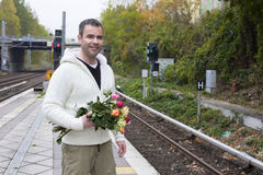 Man waiting at train station with flowers Royalty Free Stock Image