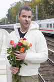 Man waiting at train station with flowers Stock Photos