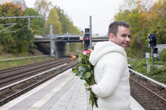 Man waiting at train station with flowers Royalty Free Stock Photo