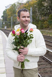 Man waiting at train station with flowers Stock Photo