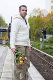 Man waiting at train station with flowers Stock Images