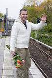 Man waiting at train station with flowers Royalty Free Stock Photography