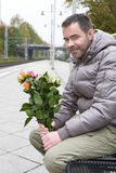 Man waiting at train station with flowers Stock Image