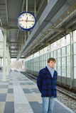 A man waiting for a train under a clock Stock Images