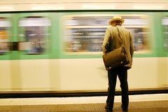 Man waiting for tube. A view of a man wearing a jacket and hat and carrying a bag over his shoulder, standing alone on a subway platform as a train rushes by Stock Photos