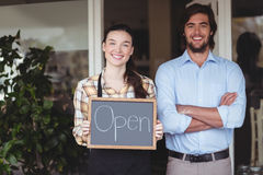 Man and waitress holding chalkboard with open sign Stock Photography