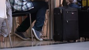 Man waits with his luggage while taking a break in travel. A typical scene at an airport or mass transit terminal stock video footage