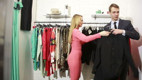 A man waits for his woman chooses a dress in a store. man holding a lot of clothes. husband wants to leave. Man is bored of women trying clothes while shopping stock video