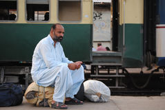 Man waits at station, trains delayed. Royalty Free Stock Photos