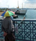 Man waits to catch fish on Galata Bridge by Bosphorus in Istanbul Royalty Free Stock Photos