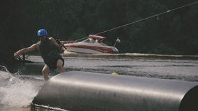 Man wakeboard slides on the tube. Young boy riding a wake board stock video