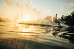 Man wakeboarding on a lake. Low angle shot of man wakeboarding on a lake. Man water skiing at sunset Royalty Free Stock Photography