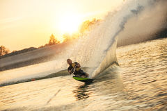 Man wakeboarding on a lake. Waterskier moving fast in splashes of water at sunset. Man wakeboarding on a lake Royalty Free Stock Photo