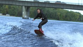 Man wakeboarding on river waves under city bridge in slow motion. Rider going fast on wakeboard on river. Extreme sportive hobby. Extreme vacation in movement stock video footage