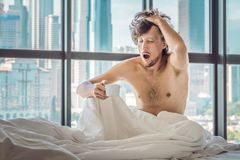 Man wakes up in the morning in an apartment in the downtown area stock photography