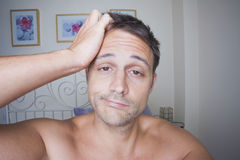 Man waking up. Man in his bedroom waking up and scratching his head Royalty Free Stock Photos