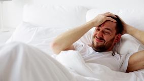 Man waking up in bed at home stock video footage