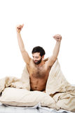 Man waking up in bed and stretching his arms. Royalty Free Stock Photo