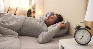 Man waking up in bed. Young man stretching and waking up in bed stock footage