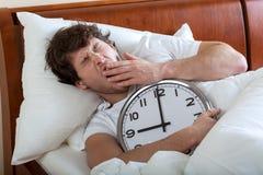 Man waking up. Man holding a big clock and waking up Stock Photo