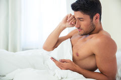 Man waking up and holding smartphone Stock Photos