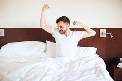 Man waking up in the morning. Handsome young man waking up and stretching on his bed right after waking up in the morning Stock Photos