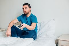 Man sitting on the bed and watching tv. Man waking up in the morning and watching tv , vintage colr filter added Stock Image