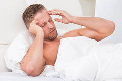 Man waking up with a nasty headache Royalty Free Stock Images