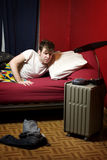 Man waking up to his alarm clock. Young man waking up to his alarm clock Stock Image