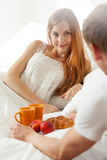Man waking up woman by serving her a breakfast Royalty Free Stock Photos