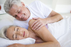 Man waking woman lying in bed sleeping Stock Images
