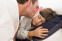 Man waking young boy in bed with kiss Stock Photography