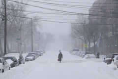 Man walk along snow covered street Royalty Free Stock Images