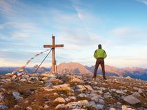 Man walk along the wooden cross at a mountain peak built to Alps victiims. Cross on top Royalty Free Stock Photography