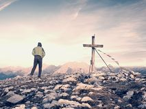 Man walk along the wooden cross at a mountain peak built to Alps victiims. Cross on top Stock Image
