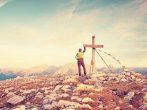 Man walk along the wooden cross at a mountain peak built to Alps victiims. Cross on top Royalty Free Stock Images