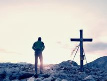 Man walk along the wooden cross at a mountain peak built to Alps victiims. Cross on top Royalty Free Stock Image