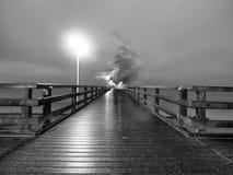 Man walk in autumn mist on wooden pier above sea. Depression, dark  atmosphere. Man ghost walk in autumn mist on wooden pier above sea. Depression, dark Stock Images